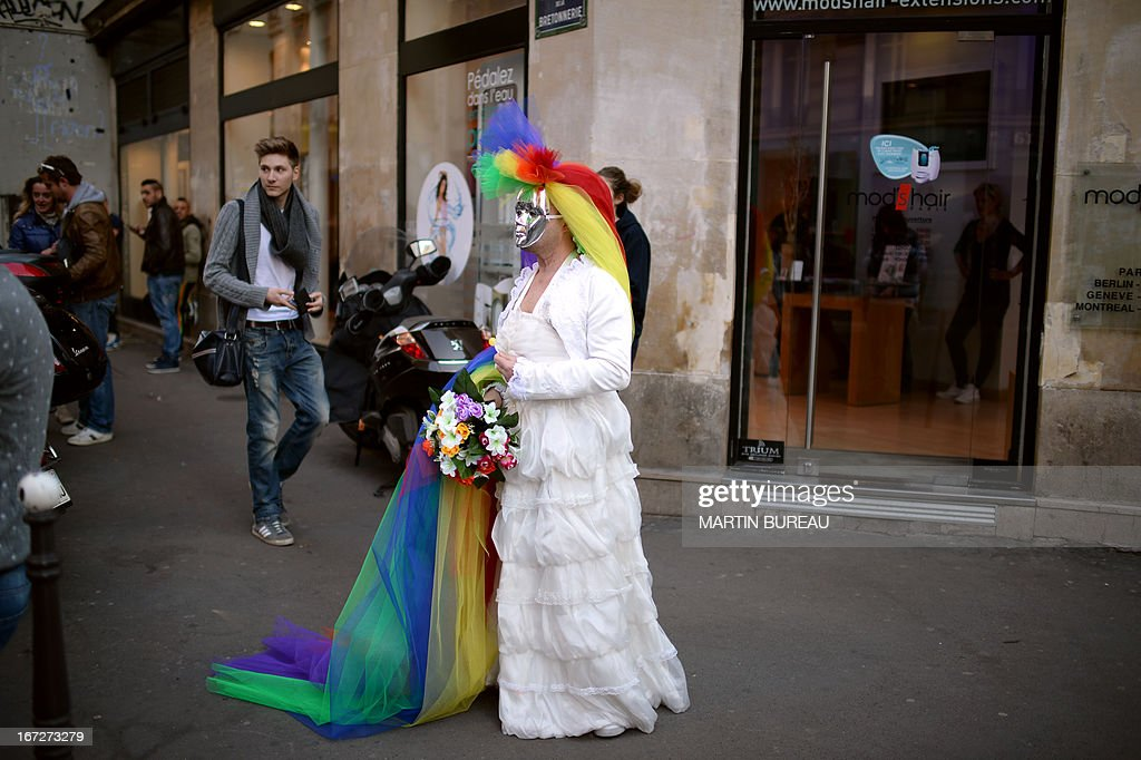 A person donns a wedding dress and sports a mask and colourful headress stands on April 23, 2013 in Paris some hours after the French National Assembly adopted a bill legalising same-sex marriages and adoption for gay couples, defying months of opposition protests. In its second and final reading, a majority of lawmakers approved the bill by a vote of 331 to 225. AFP PHOTO / MARTIN BUREAU
