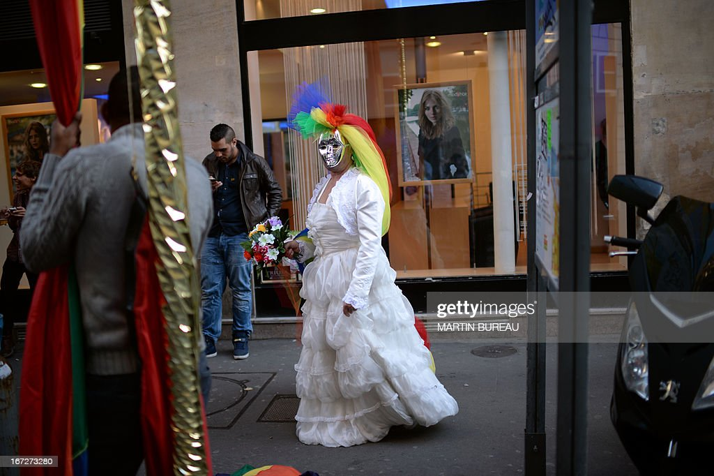 A person donns a wedding dress and sports a mask and colourful headress stands on April 23, 2013 in Paris some hours after the French National Assembly adopted a bill legalising same-sex marriages and adoption for gay couples, defying months of opposition protests. In its second and final reading, a majority of lawmakers approved the bill by a vote of 331 to 225.