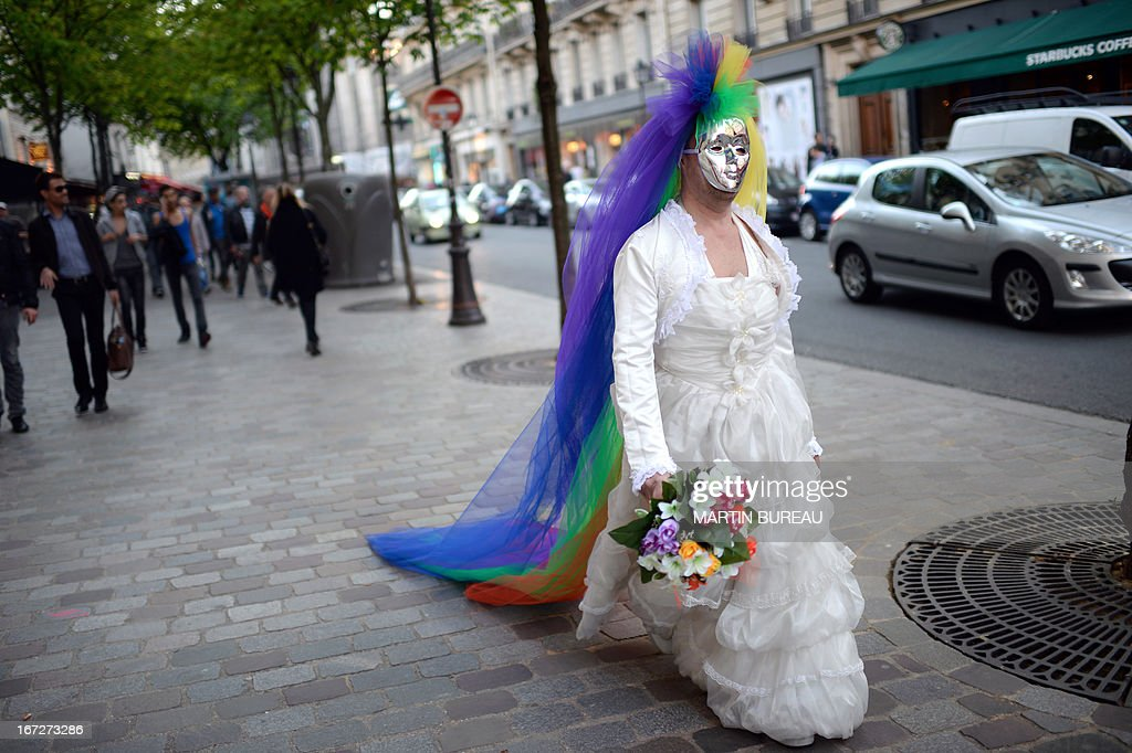 A person donns a wedding dress and sports a mask and colourful headress walks on April 23, 2013 in Paris some hours after the French National Assembly adopted a bill legalising same-sex marriages and adoption for gay couples, defying months of opposition protests. In its second and final reading, a majority of lawmakers approved the bill by a vote of 331 to 225. AFP PHOTO / MARTIN BUREAU