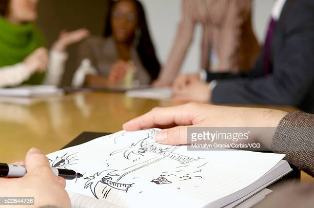 Person doodling during business meeting