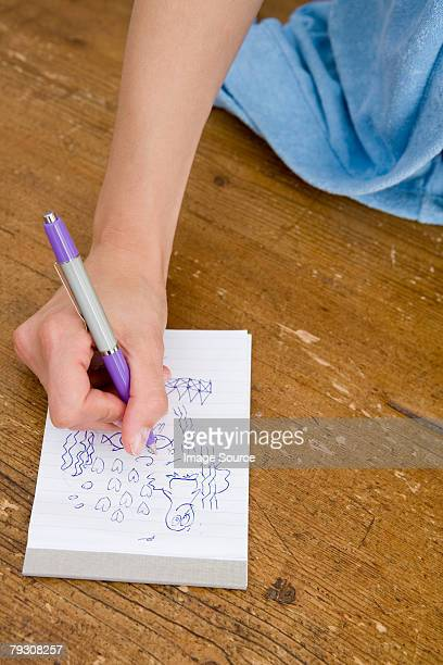 Person drawing on notepad