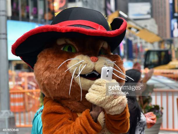 A person dressed as a cartoon character uses a cell phone to take a photograph of tourists with other characters July 28 2014 in New York's Times...