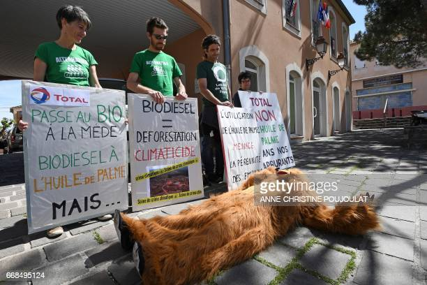 A person dressed as an orangutan lays on the ground by people holding placards reading 'Total passes to organic at the Mede oil palm biodiesel but'...