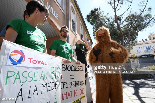 A person dressed as an orangutan walks by people holding placards as they take part in a rally in front of the ChateauneuflesMartigues' townhall on...