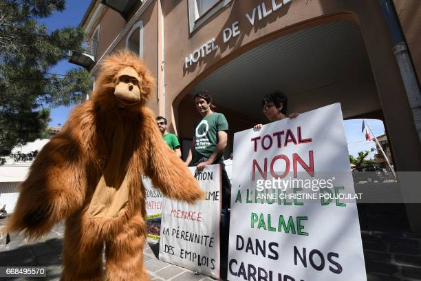 A person dressed as an orangutan walks by people holding placards reading 'Total no to palm oil in our fuel' as they take part in a rally in front of...