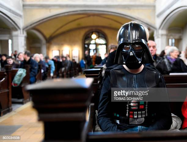 A person dressed as the Darth Vader character sits inside the zion church in Berlin on December 20 2015 during a Star Wars'themed church service...