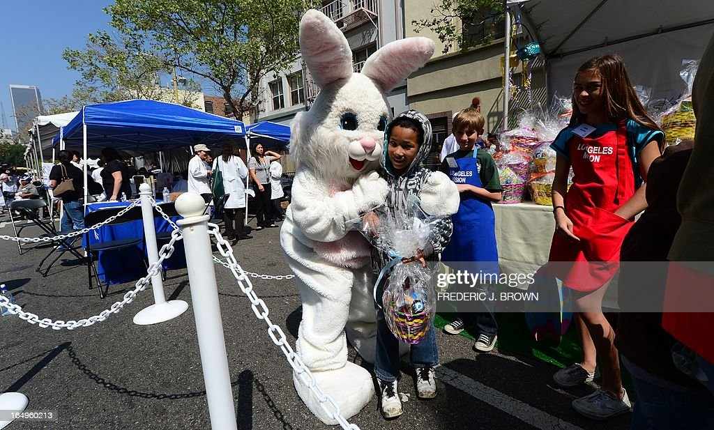 A person dressed as the Easter Bunny embraces a child as people gather at the Los Angeles Mission's Good Friday event on Skid Row on March 29, 2013 in Los Angeles, California. Celebrities and volunteers joined together in giving something back to this community of the homeless, among the largest in the US, who were fed a fully-prepared meal and had the opportunity to be given foot washing and hygiene kits. Foot washing, a symbolic ritual of humbleness and respect derived from Jesus Christ's washing of his disciples feet at the Last Supper, was offered by the Los Angeles Health Center and volunteers. AFP PHOTO/Frederic J. BROWN