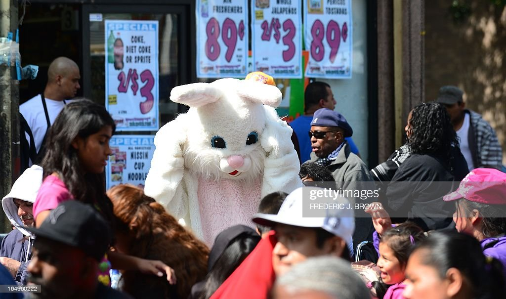 A person dressed as the Easter Bunny greets people at the Los Angeles Mission's Good Friday event on Skid Row, March 29, 2013 in Los Angeles, California. Celebrities and volunteers joined together in giving something back to this community of the homeless, among the largest in the US, who were fed a fully-prepared meal and had the opportunity to be given foot washing and hygiene kits. Foot washing, a symbolic ritual of humbleness and respect derived from Jesus Christ's washing of his disciples feet at the Last Supper, was offered by the Los Angeles Health Center and volunteers. AFP PHOTO/Frederic J. BROWN