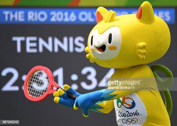 A person dressed as Vinicius the mascot of the Rio 2016 Olympic Games holds a tennis racket on the Centre Court of the Olympic Tennis Centre in Rio...