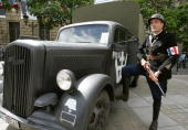 A person dressed as World War II French policeman poses next to an Opel Blitz truck used by the German army 19 August 2004 in Paris during as part of...