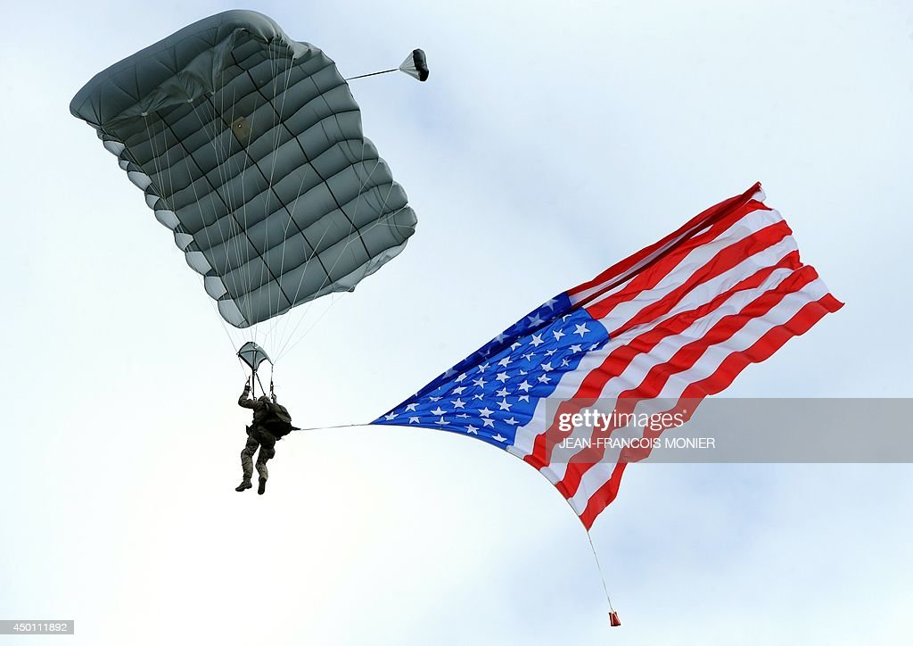 A person dressed in a WWII-era uniform parachutes from a C-47 military transport airplane with an American flag at Utah Beach in Sainte-Marie-du-Mont, northern France, on June 5, 2014, on the eve of the 70th anniversary of the World War II Allied landings in Normandy. June 6, 2014 marks the 70th anniversary of D-Day and 'Operation Overlord', a vast military operation by Allied forces in Normandy, which turned the tide of World War II, eventually leading to the liberation of occupied France and the end of the war against Nazi Germany. AFP PHOTO / JEAN-FRANCOIS MONIER