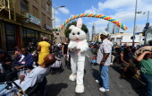 A person dressed in an Easter Bunny costume arrives to greet the homeless on Skid Row awaiting their annual Good Friday meal hosted by the LA Mission...