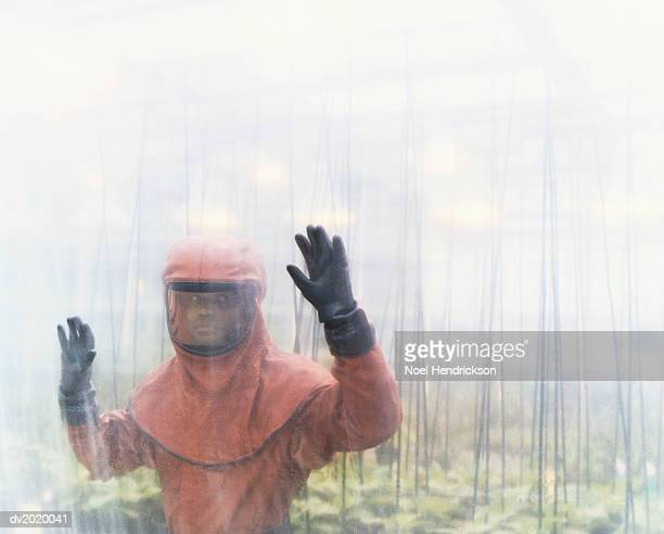 Person Dressed in Protective Clothing Standing in a Greenhouse