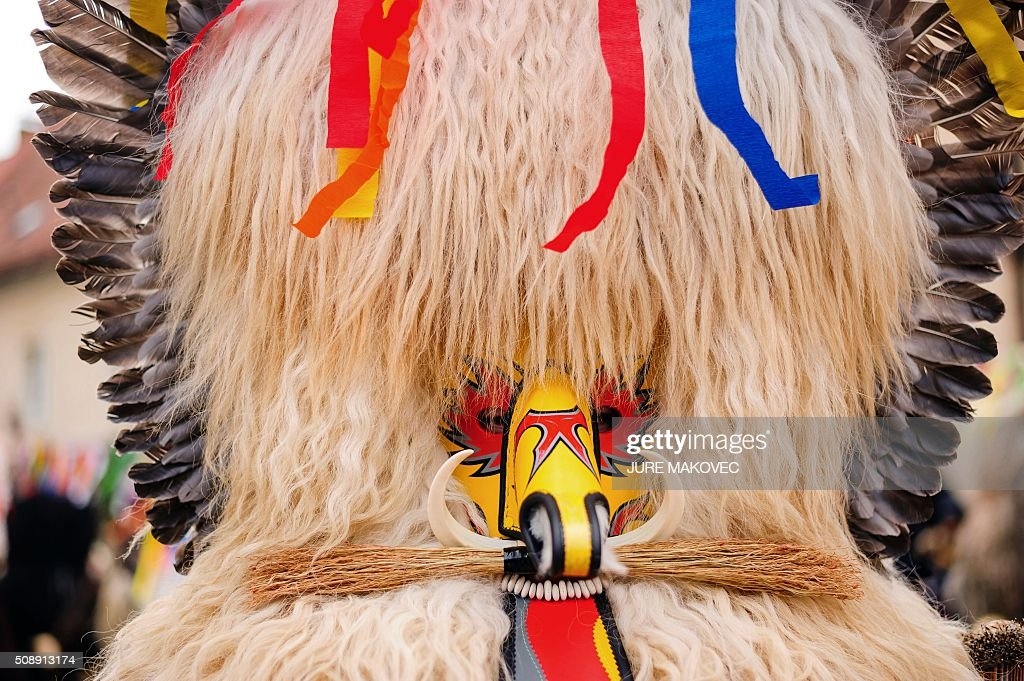 A person dressed in traditional Slovenian Kurent costumed parades during the Ptuj carnival in Ptuj, on February 7, 2016. Kurents are characters wearing sheep skin, a mask with a long red tongue, a cow bell, and multi-coloured ribbons on the head, intended to drive away evil spirits of the winter. The Ptuj carnival is the largest in Slovenia and last 11 days. / AFP / JURE MAKOVEC