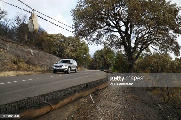 A person drives a car past devastated land following a fire in Biguglia on the French Mediterranean island of Corsica on July 26 2017 France asked...