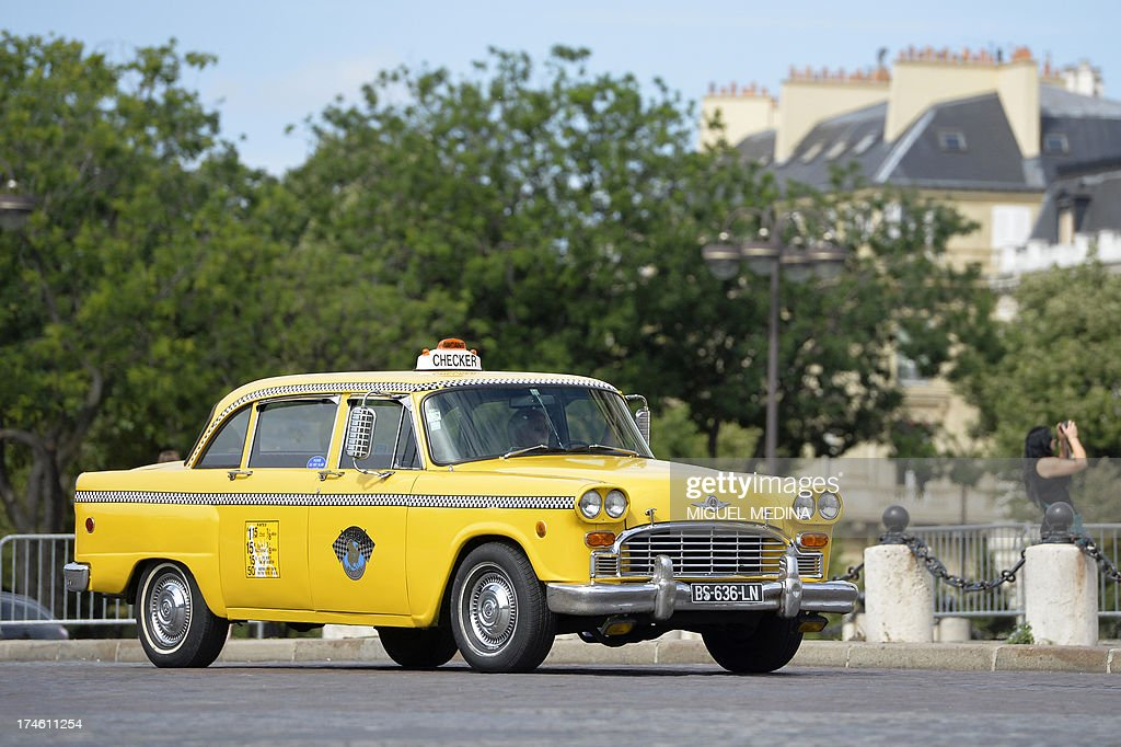 A person drives a Checker Motors New York City Yellow Taxi car in Paris, on July 28, 2013, during a vintage cars parade as part of the sixth summer edition of the 'Traversee de Paris Estivale' ('Summer Paris Crossing'), the largest gathering of classic vehicles in the French capital streets.