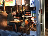 A person eating at a table inside a Bagel and Sandwich Store behind a glass window which has a Help Wanted sign posted along with other promotions...