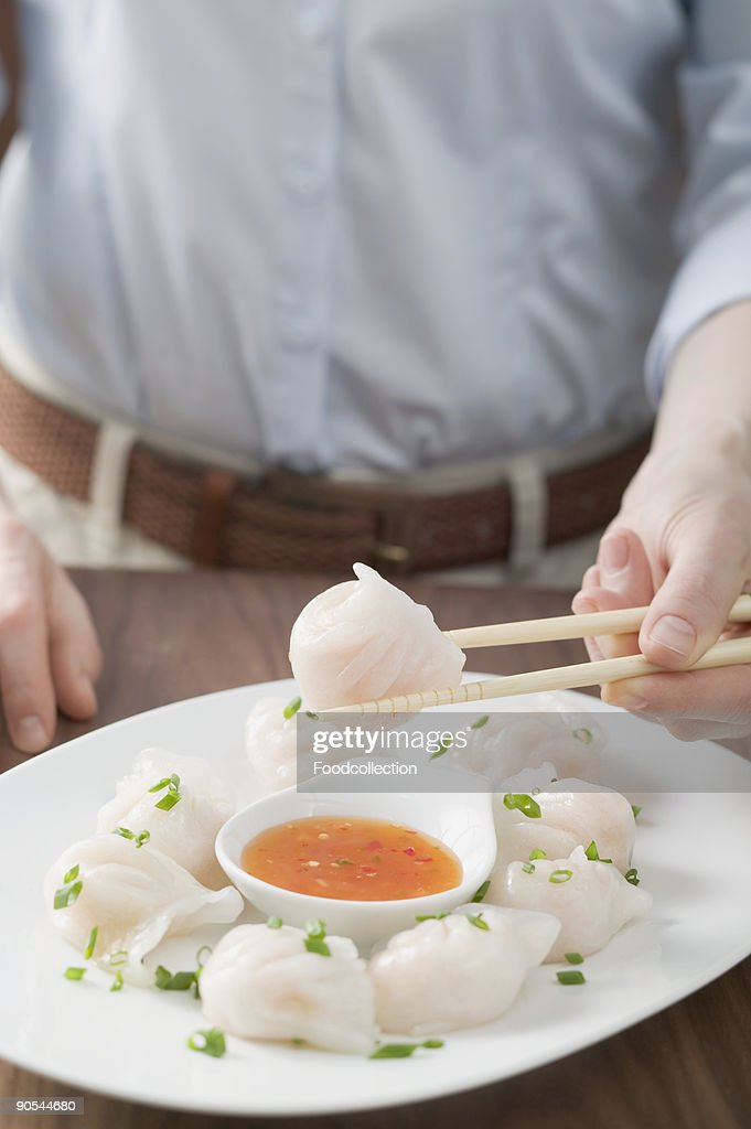 Person eating dim sum with chilli sauce, close up : Stock Photo