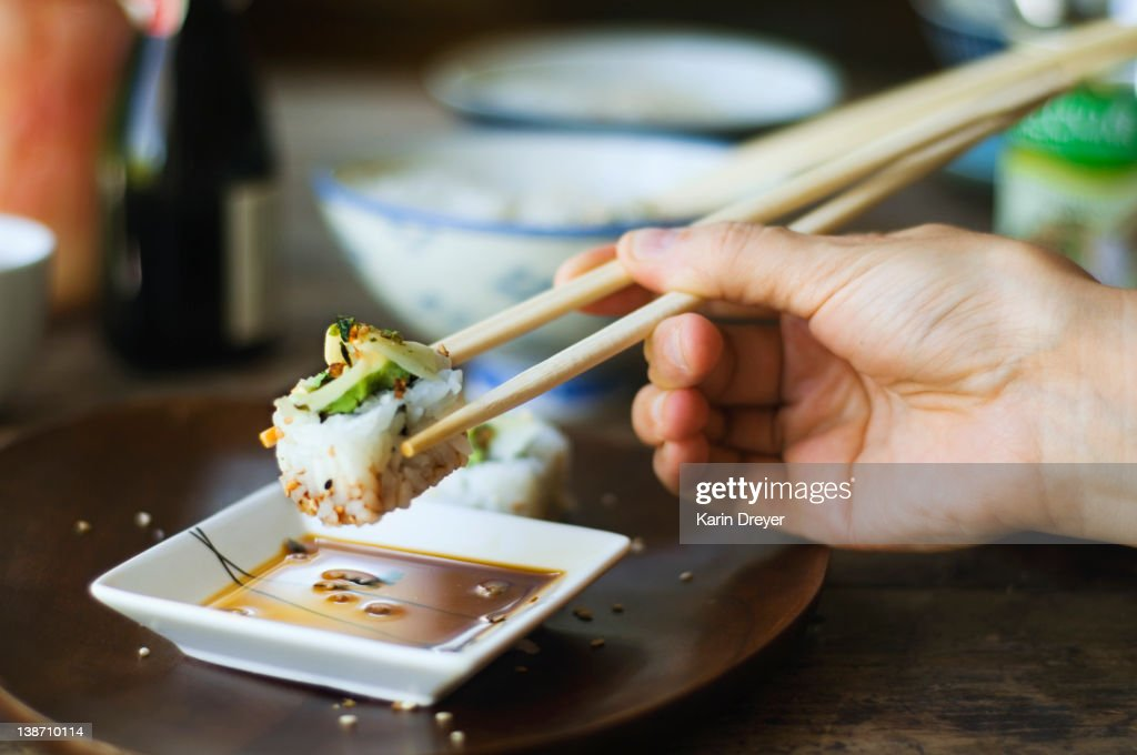 Person eating sushi with chopsticks : Stock Photo