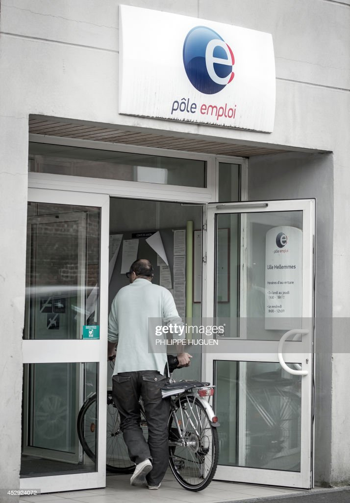 A person enters a French Pole Emploi employment agency on July 30, 2014 in Villeneuve d'Ascq, northern France.