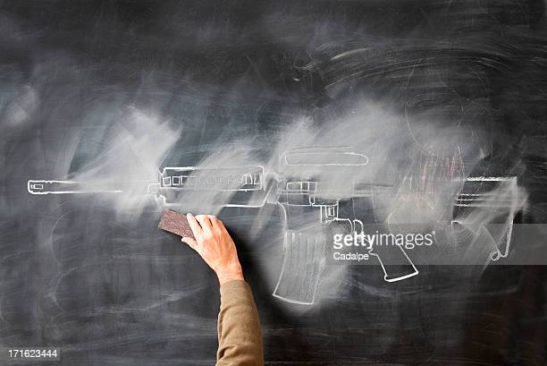Person erasing chalk drawing of gun on blackboard