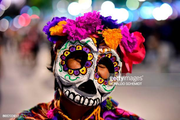 TOPSHOT A person fancy dressed as 'Catrina' takes part in the 'Catrinas Parade' along Reforma Avenue in Mexico City on October 22 2017 Mexicans get...
