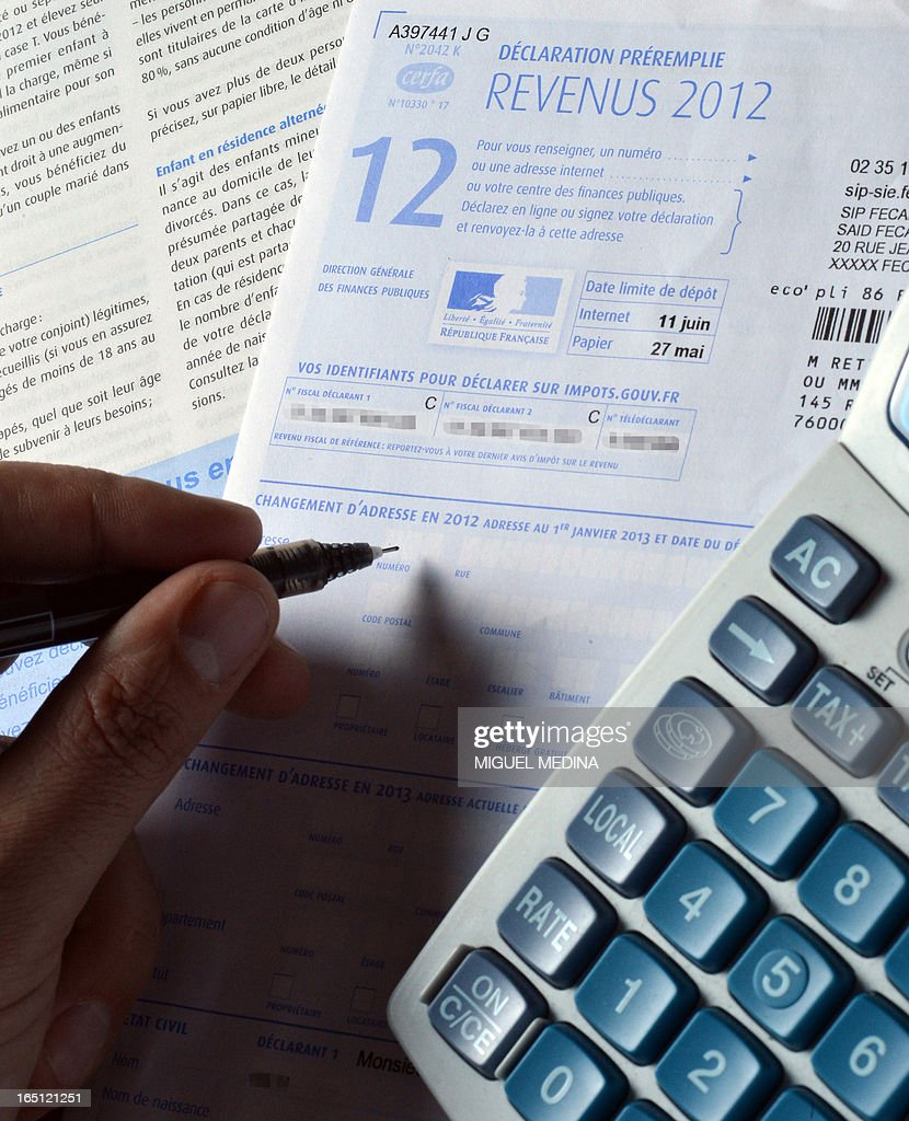 A person fills out a pre-filled tax declaration for the 2012 income tax on March 31, 2013 in Paris. AFP PHOTO / MIGUEL MEDINA