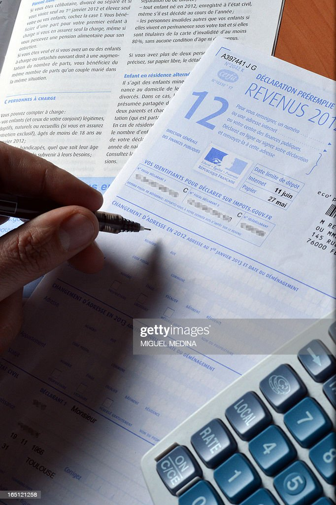 A person fills out a pre-filled tax declaration for the 2012 income tax on March 31, 2013 in Paris.