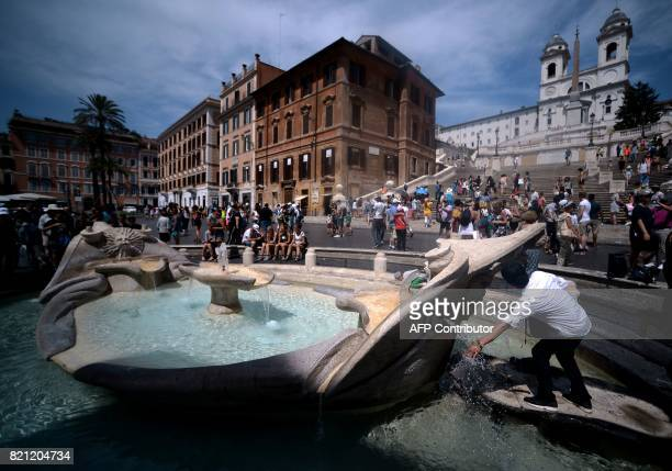 A person fills up a bottle with water off the barcaccia Fountain in Rome's Piazza di Spagna on July 23 2017 Several areas of Italy including the Po...