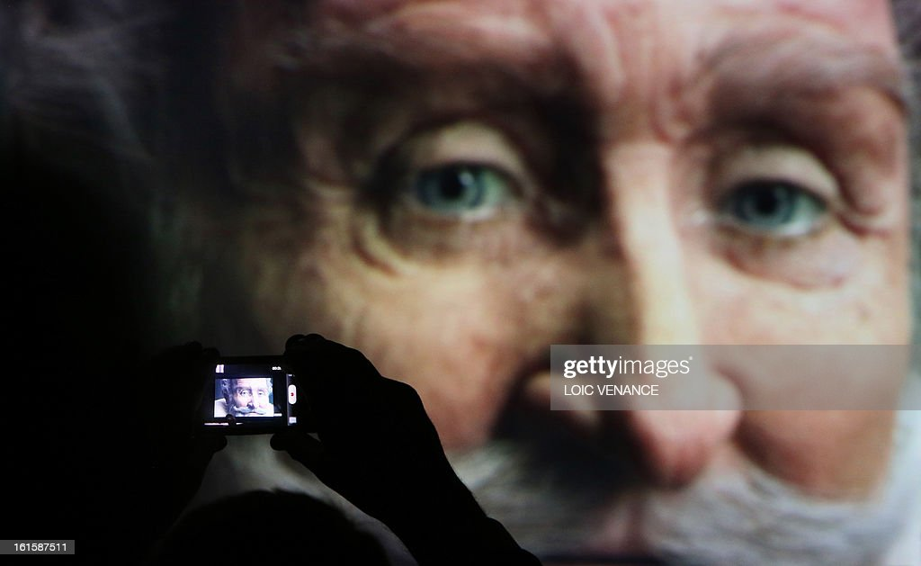 A person films a screen bearing a reconstruction of the head of French King Henri IV (1553-1610) during a press conference in Paris on February 12, 2013. This reconstruction was made three years after a panel of forensic scientists identified the skull of the king who was murdered at the age of 57 on May 14, 1610, by a fanatic. Scientists headed by France's Philippe Charlier found a common genetic profile between the mummified head of Henri IV and dried blood from his descendant, Louis XVI. AFP PHOTO LOIC VENANCE