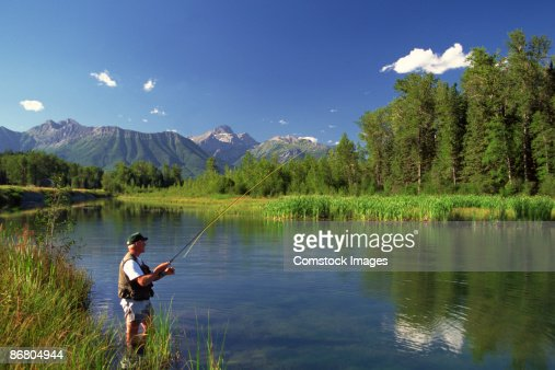 Person Fly Fishing In Mountain Lake Stock Photo