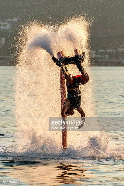 Person Flyboarding In Sea During Sunset