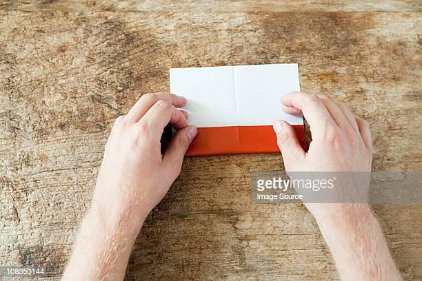 Person folding paper