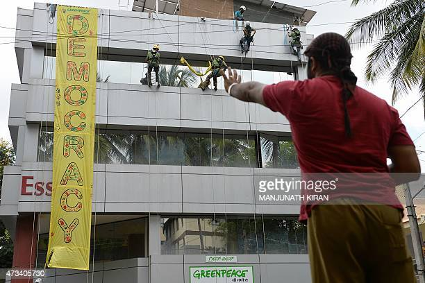 A person gestures as he watches as activists of GreenPeace rappell down their office building where they are head quartered to unfurl banners...