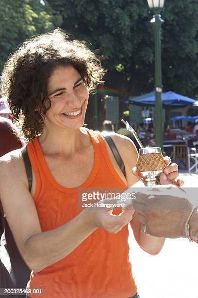 Person giving a bowl of yerba mate to a young woman