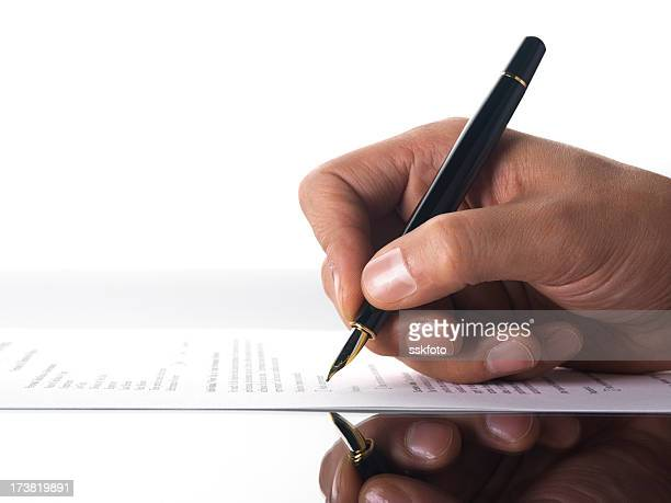 A person grasping a pen and writing