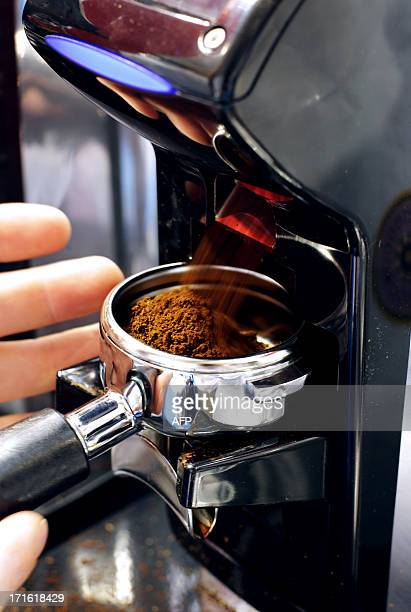 A person grinds grains coffee beans during the exhibition 'World of coffee' on June 27 in Nice southeastern France AFP PHOTO / JEAN CHRISTOPHE...