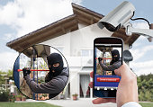 Person Hand Holding Mobile Phone Detecting Burglar In Security System With Surveillance Camera Behind