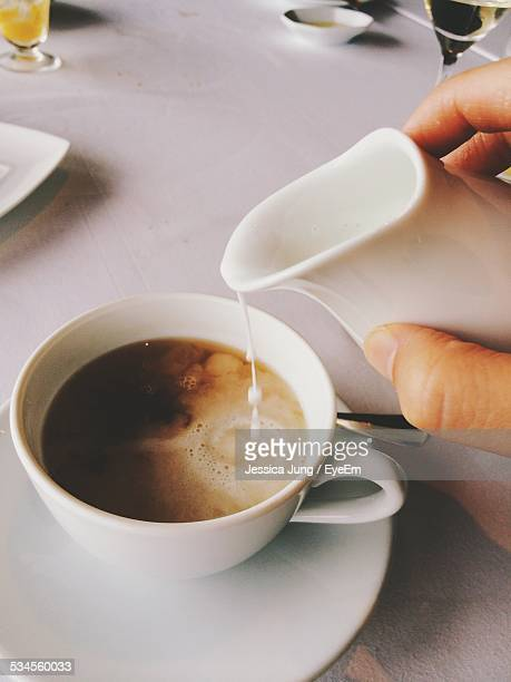 Person Hand Pouring Milk In Coffee