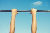 Person hanging on horizontal bar against sky.