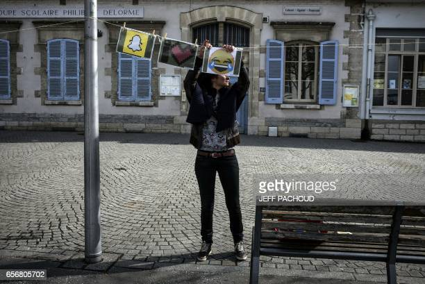 TOPSHOT A person hangs a drawing on a clothesline during the 10th edition of the 'La Grande Lessive' international event on March 23 2017 in Lyon...