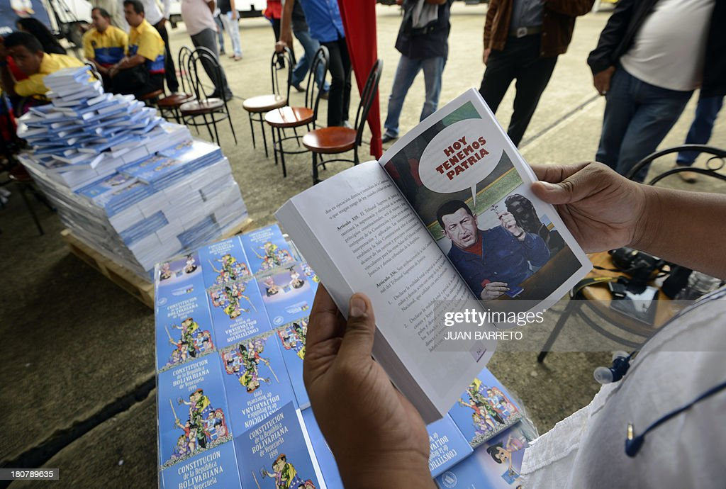 A person has a look at a Venezuelan Constitution with drawings depicting late President Hugo Chavez, as hundreds is copies are delivered at a school in Caracas, on September 16, 2013. AFP PHOTO