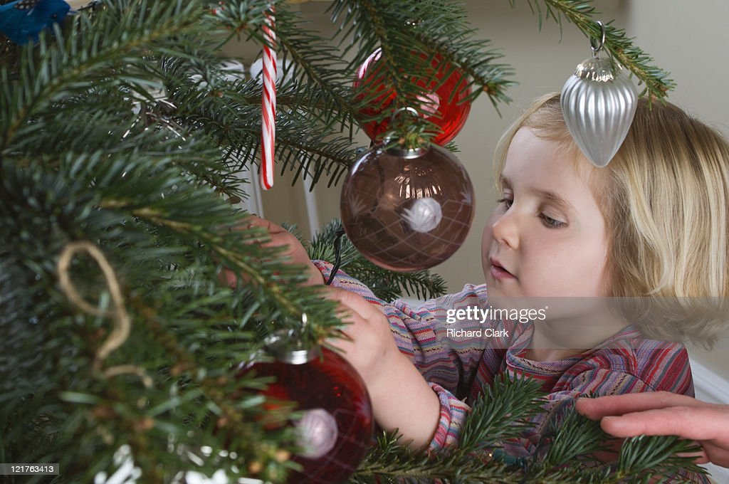 Person helping child hang christmas decorations : Stock Photo