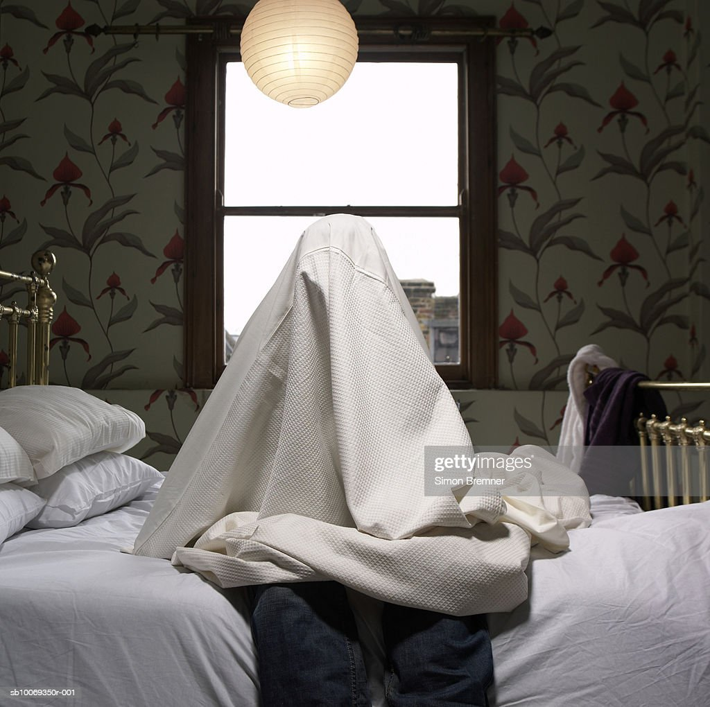 Person hiding under sheet on bed : Stock Photo