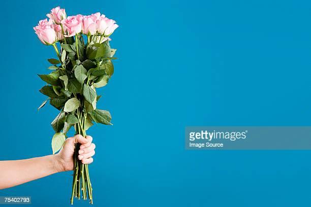 Person hält einen Strauß Rosen