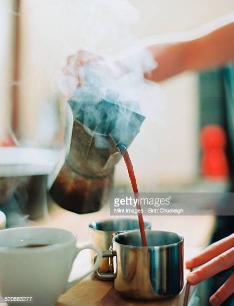 A person holding a coffee percolator and pouring hot coffee into cups.