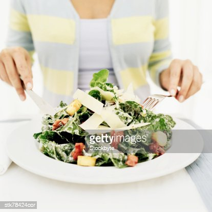Person holding a fork and knife on a plate of vegetables : Stock Photo