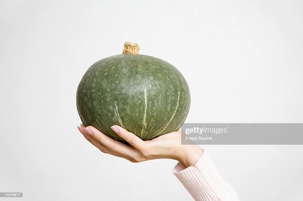Person holding a kabocha pumpkin