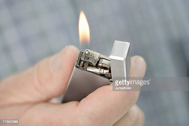 Person holding a lit cigarette lighter