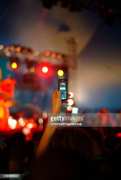 Person holding a mobile phone up to photograph a concert UK 2007